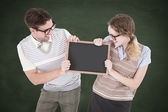 Geeky hipster couple holding little blackboard — Stock Photo