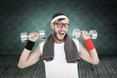 Geeky hipster lifting dumbbells in sportswear — Stock Photo