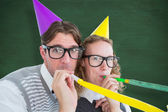 Geeky hipster couple blowing party horn — Stock Photo