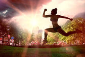 Composite image of fit brunette running and jumping — Stock Photo