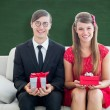 Cute geeky couple smiling and holding gift — Stock Photo #69050167