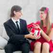 Cute geeky couple smiling and offering gift — Stock Photo #69055345