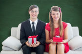 Cute geeky couple smiling and holding gift — Stock Photo