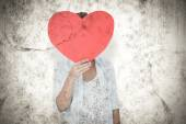 Composite image of woman holding heart card — Stock Photo