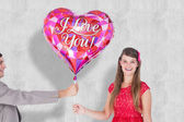 Geeky hipster offering red heart shape balloon — Stock Photo
