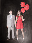 Unsmiling geeky couple standing hand in hand — Stock Photo