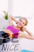 Smiling fit blonde doing sit ups with exercise — Stock Photo