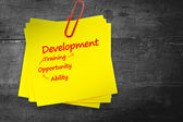 Development list against sticky note — Stock Photo