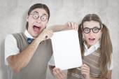 Composite image of geeky hipsters holding a poster — Stock Photo