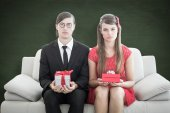 Unsmiling geeky couple with gift — Stock Photo