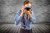 Geeky hipster holding a retro camera — Stock Photo