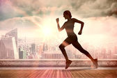 Composite image of pretty fit blonde jogging  — Stock Photo