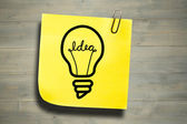 Light bulb against sticky note — Stock Photo