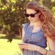 Pretty blonde girl using phone in the park — Stock Video #69512433