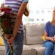 Daughter surprising her mother with flowers — Stock Video #69513501