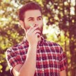 Handsome hipster boy smoking an electronic cigarette — Stock Video #69518781