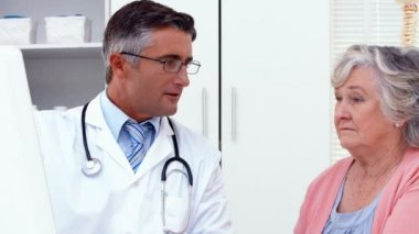 Doctor explaining something to his patient — Stock Video