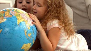 Cute siblings looking at globe — Stock Video