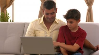 Father and son using laptop on couch — Stock Video