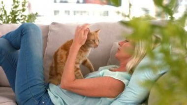 Happy blonde with pet cat on sofa — Stock Video