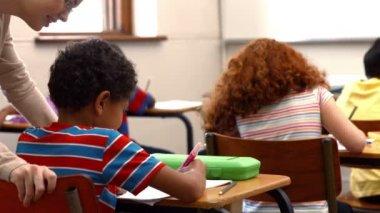 Teacher helping a little boy during class — Stock Video