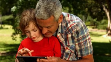 Father and son using tablet in park — Stock Video