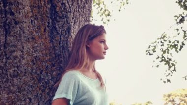 Pretty girl smiling at camera in park — Stock Video