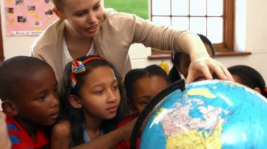 Teacher looking at globe with pupils — Stock Video
