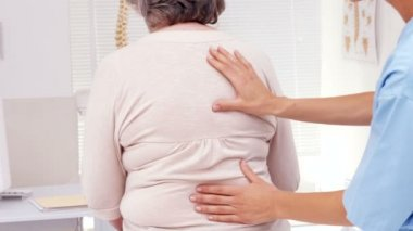 Physiotherapist examining elderly patients back — Stock Video