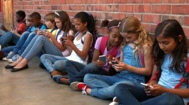 Schoolchildren sitting outside using phones — Stock Video