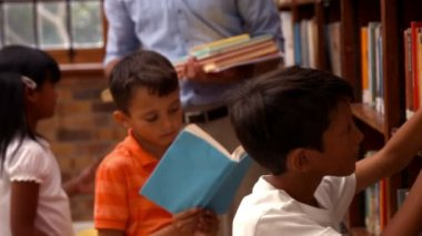 Cute pupils with teacher in library — Stock Video