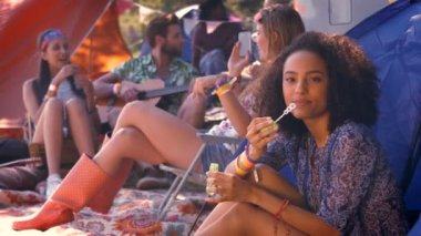Carefree hipster blowing bubbles in tent — Stock Video