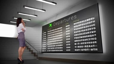 Businesswoman looking at departures board — Stock Video