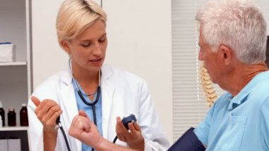 Doctor taking blood pressure of elderly patient — Stock Video