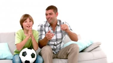 Father and son with football watching tv — Stock Video
