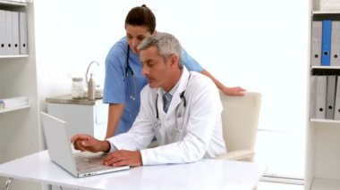 Doctor using computer keyboard at desk — Stock Video