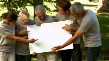 Volunteers in the park showing sign — Stock Video