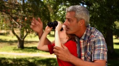 Father and son using binoculars in park — Stock Video