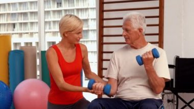 Trainer helping senior citizen work out — Stock Video