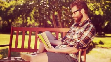 Handsome hipster boy reading in the park — Stock Video