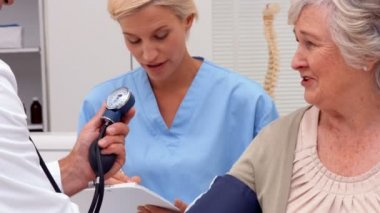Doctor taking blood pressure of patient with nurse — Stock Video