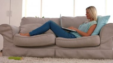 Happy blonde with laptop on sofa — Stock Video