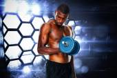 Young man lifting dumbbell — Stockfoto