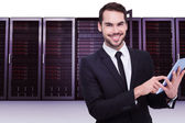 Businessman using his tablet against server towers — Stock Photo