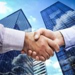 Men shaking hands against skyscraper — Stock Photo #73185441