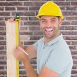 Worker using measure tape to mark on plank — Stock Photo #73185687
