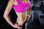 Composite image of female bodybuilder posing in pink sports bra — Stock Photo
