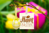 Happy easter graphic against gift box and tulips — Stock Photo