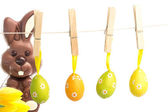 Hanging easter eggs against chocolate bunny — Fotografia Stock