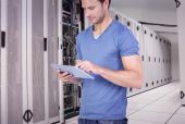 Man scrolling through tablet pc against data center — Stock Photo